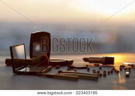 Minimal make up set on a table in the background of a sunset. Visage tools.