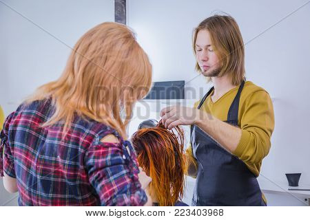 Two professional hairdressers, stylists drying client hair with blow-dryer at salon, studio. Beauty and haircare concept