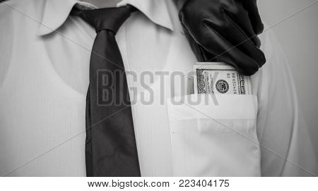 A thief takes a wallet with a cash from a pocket of a man in a suit, a businessman, a crime, a pocket