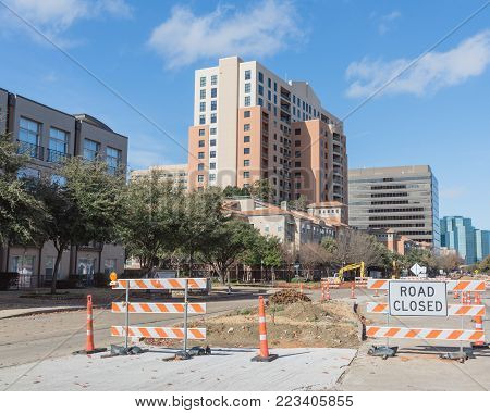 Road closed sign in Downtown Irving, Texas, USA under cloud blue sky. Barricade closures, cones with construction equipments and high-rise building in background.