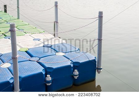 Plastic pontoon with the rope fence is floating on the small lake in the urban park.