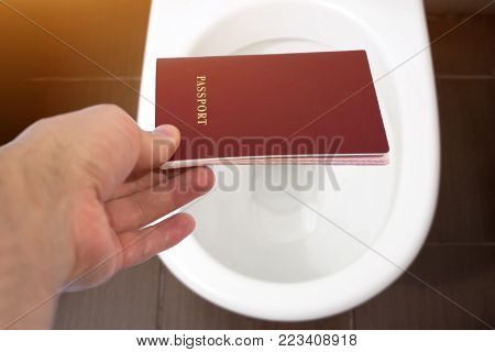 Hand Holds The Citizen's Passport Over The Toilet, Throw Out His Passport. Concept - Change Of Citiz