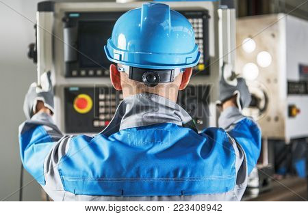 Caucasian CNC Operator in Front of Machine Operating Console. Metalworking Concept.
