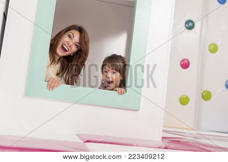 Cheerful mother and daughter hiding in a small wooden house in a playroom, peeking through a window and making faces