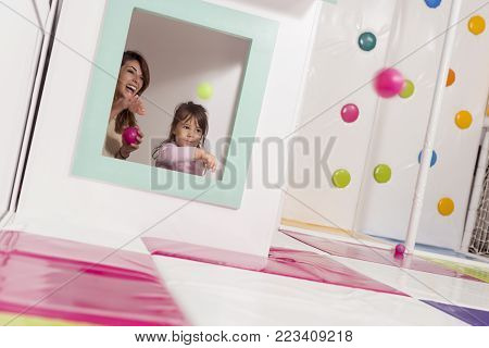 Mother and daughter playing in a playroom, hiding in a small wooden house, throwing balls through the window. Focus on the mother