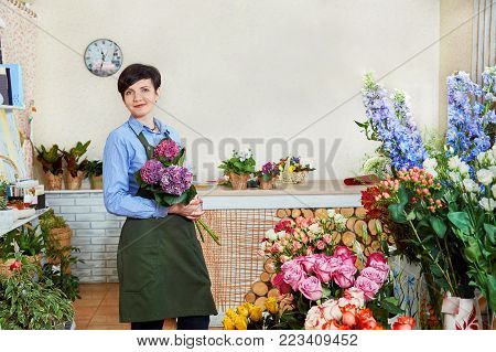 young female florist working in flower shop. Small flower business. Women working in flower shop. Smiling young female florist working in flower shop. Place for text or ads