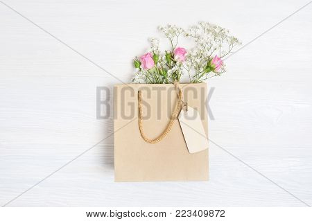 Mock up Composition paper bag and tag of white flowers rustic style, for St. Valentine's Day with a place for your text. Flat lay, top view photo mock up.