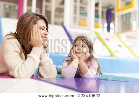Beautiful mother and daughter lying on the playroom floor, taking a break and planing fun activities to do. Focus on the daughter