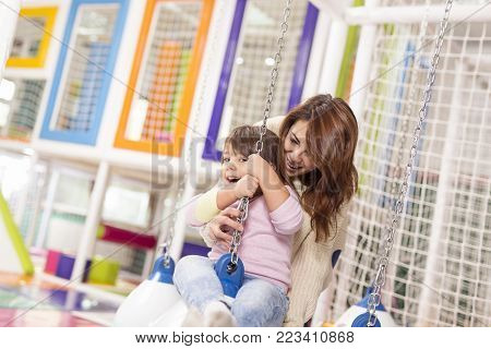 Mother holding her daughter while she is happily enjoying swinging on a giant ball in a playroom. Focus on the daughter