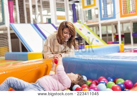 Cheerful mother and daughter playing in a playroom, in a pool filled with colorful balls