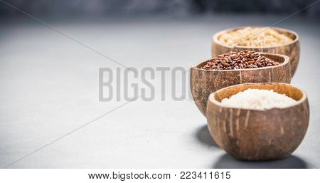 Assortment of different rice in bowls: Rice berry, Brown rice and Risotto rice on grey concrete background.