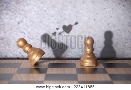 Shadow of a love heart cupid arrow aiming at falling chess pawn