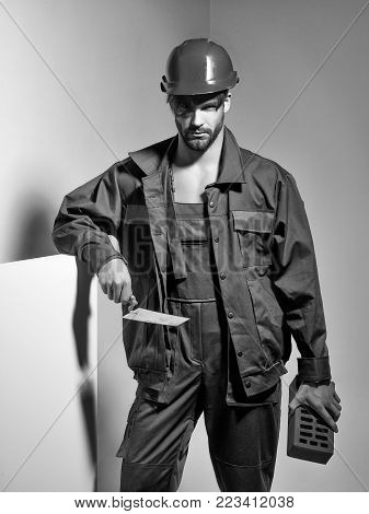 Handsome man builder construction mason worker bricklayer in orange hard hat and boilersuit keeps brick and trowel on grey background