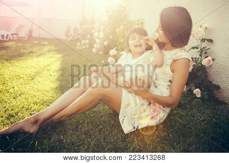 Mothers day concept. Mom and child smiling at blossoming rose flowers. Family love and care. Nurturing and future. Woman with baby girl sitting on green grass.