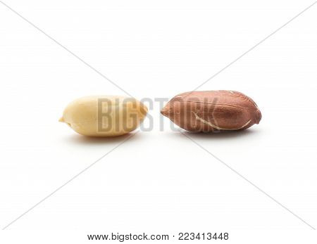 Two peanuts one raw without husk isolated on white background compare