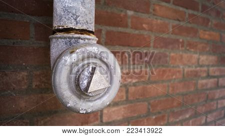 a old used steel metal valve with parts of the valve rusty hanging from the top against a baked brick background