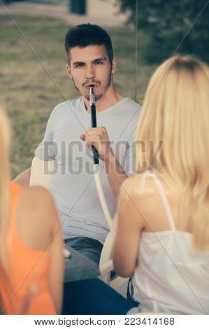 Man Vapor Hookah Pipe With Girls In Shisha Bar Lounge. Celebration, Party Concept. Addiction, Bad Ha