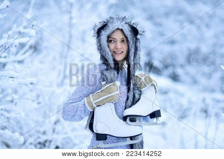 Woman happy smile with figure skates at trees in snow. Sport, activity, health. Girl with skating shoes in winter clothes in snowy forest. Ice skating concept. Vacation, holidays, hobby, lifestyle.