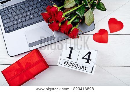 Top view of bouquet of red roses, red gift box, wood calendar february 14, two hearts and open laptop computer on white table. Greeting card for Valentines Day. Flat lay