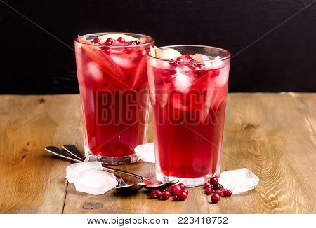 Glass of Cold Winter Drink With Fresh Cranberry and Apple Cold Horizontal Photo Wooden Background Copy Space Berry Ice Tea