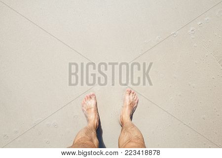 Wet male feet stand on white coastal sand, top view photo