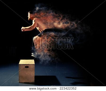 Man jumping on fit box in gym. Male with naked torso exercises jump on the dark background.