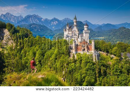 Classic view of famous Neuschwanstein Castle with male tourist enjoying the view from a steep cliff, Füssen, Bavaria, Germany