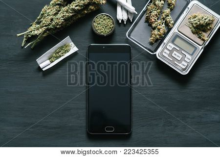 Smartphone with black screen for chroma key, chroma key against the background of cannabis flowers, concept of online