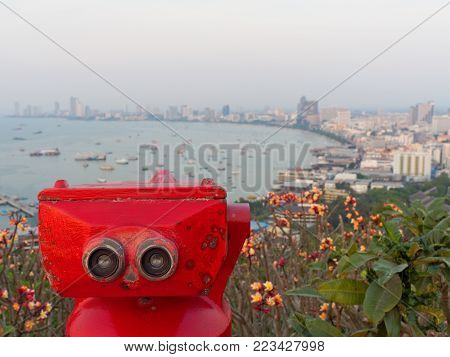 Red binocular on Pattaya beach showing explore and discover new place in tourism industry with sky, sea, and coast on background