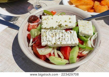 Village greek salad dish on white wooden table in greek tavern. Horizontal. Daylight. Close-up.