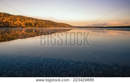 Wilderness Lake Reflections. Monocle Lake in northern Michigan with autumn foliage reflected in the calm blue water of the lake and a sunset horizon. Hiawatha National Forest, Brimley, Michigan.