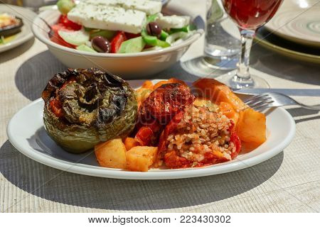 Rise stuffed fresh tomato and pepper sarved with potatoes, carrots on white wooden table in greek tavern. Horizontal. Close-up. Daylight.