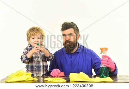 Guy with beard and mustache in rubber gloves at table. Man with cute child on white background. Kid with father holds cleaning sprays. Fatherhood concept.