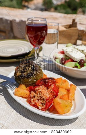 Rise stuffed fresh tomato and pepper sarved with potatoes carrots near glass of red wine, greek salad dish on white wooden table in greek tavern. Vertical. Daylight.