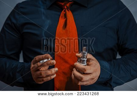 A lit cigarette in one hand of a man. In the other hand is an electronic cigarette or vape. Close-up. No smoking.