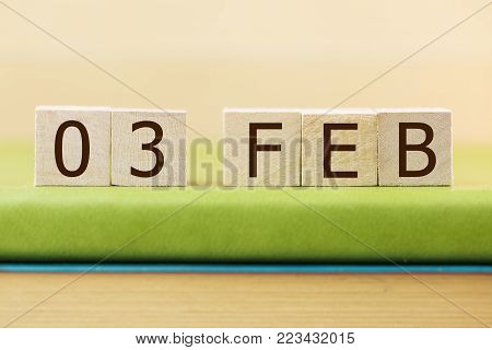 Wooden cube shape calendar for FEB 3 on green book, table.