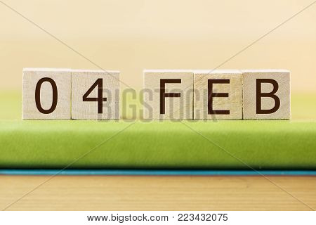 Wooden cube shape calendar for FEB 4 on green book, table.
