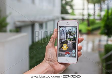 Bangkok, Thailand - Aug 7, 2016 : Hand holding Apple iphone5 mobile phone showing the Pokemon Go application at screen over the walk way with park photo blurred background on August 7, 2016, thailand