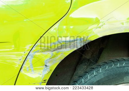 Damaged car. Yellow scratched car with damaged paint in crash accident or parking lot