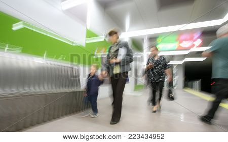 Motion blurred image of a modern metro station with unrecognizable commuters.