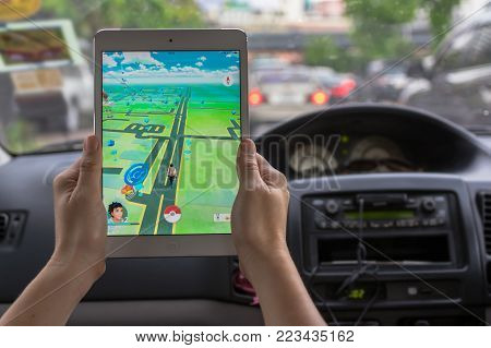 Bangkok, Thailand - Aug 7, 2016 : Hand holding Apple ipad mini2 tablet showing the Pokemon Go application at screen in the car over on the way photo blurred background on August 7, 2016, thailand