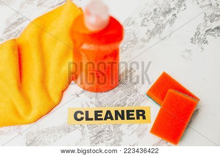 Ready for cleanup.Set of orange cleaning tools: rags, sponges, dishwashing liquid on a light concrete background. Printed cleaner inscription, flat lay, top view