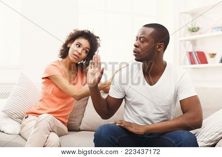 Young african-american couple making peace after quarreling at home, man still feeling offended. Family relationship difficulties concept
