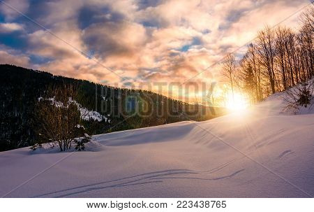 sun rising behind the snowy slope. wonderful nature winter scenery in mountainous area