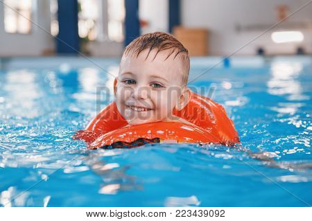 Portrait of white Caucasian child in swimming pool. Preschool boy  training to float with red circle ring in water. Healthy active lifestyle
