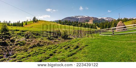 panorama of grassy meadow of rural area. gorgeous springtime landscape with forest and mountain ridge with snowy tops. haystack behind the fence near the brook
