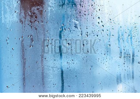 Texture of small water drops on a transparent glass. High humidity and condensation