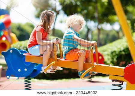 Kids climbing and sliding on outdoor playground. Children play in sunny summer park. Activity and amusement center in kindergarten or school yard. Child on colorful slide. Toddler kid outdoors.