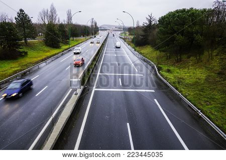 Automobile toll road with cars. Top view on an overcast day. Cash desks for payment of departure at the end of the road.