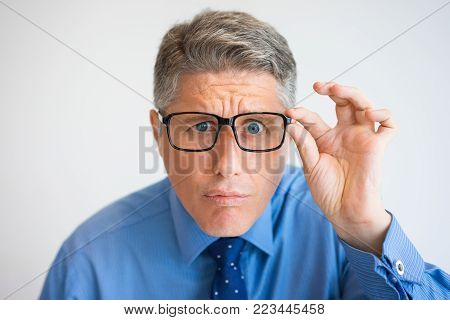 Close-up of face of mature Caucasian businessman wearing shirt and tie and eyeglasses, looking at camera and squinting. Eyesight and optics concept